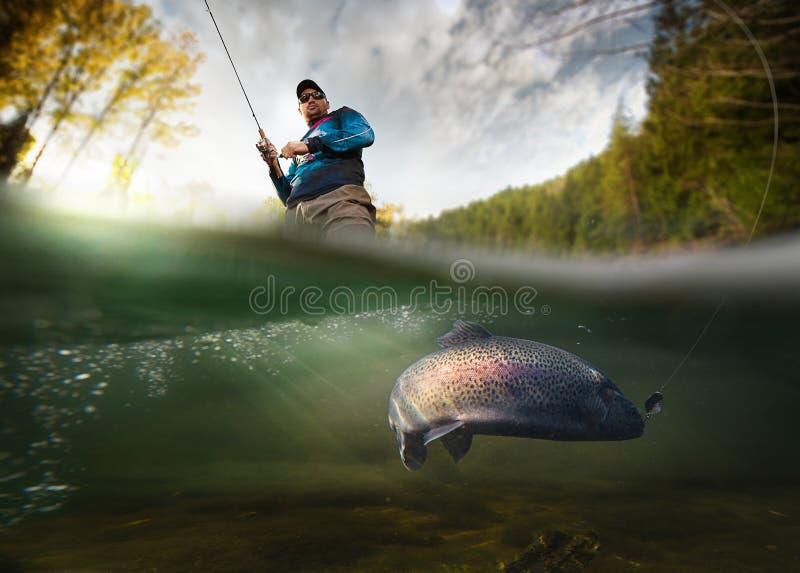 Fischer und Forelle, Unterwasseransicht lizenzfreies stockfoto