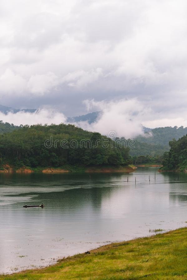 Fischer und kleines Fischerboot und Schwimmen in Knall Lang-Reservoir lizenzfreie stockfotografie