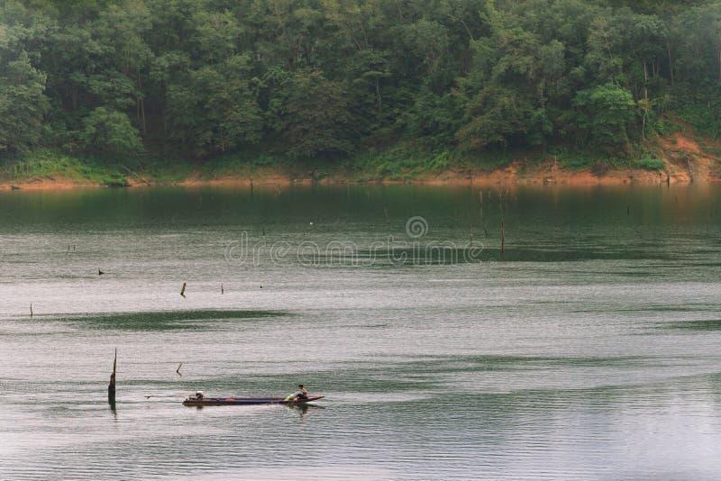 Fischer und kleines Fischerboot und Schwimmen in Knall Lang-Reservoir stockfotografie