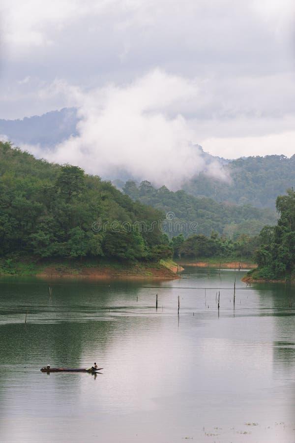 Fischer und kleines Fischerboot und Schwimmen in Knall Lang-Reservoir lizenzfreies stockfoto