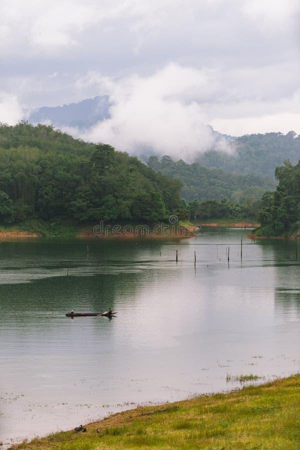 Fischer und kleines Fischerboot und Schwimmen in Knall Lang-Reservoir lizenzfreie stockfotos