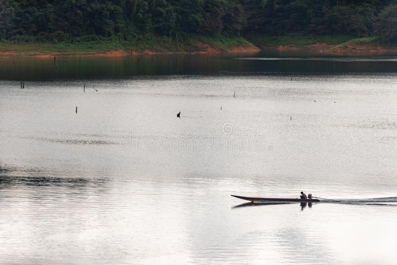 Fischer und kleines Fischerboot und Schwimmen in Knall Lang-Reservoir stockfotos