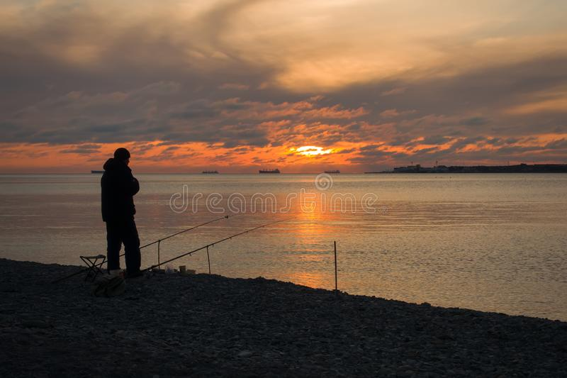 Fischer und majestätischer Sonnenuntergang über Wasser lizenzfreie stockfotografie