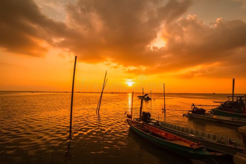 Fischerboot auf dem Meerwasser und der Sonnenuntergang, Sonnenaufgang und nette Wolke lizenzfreies stockfoto