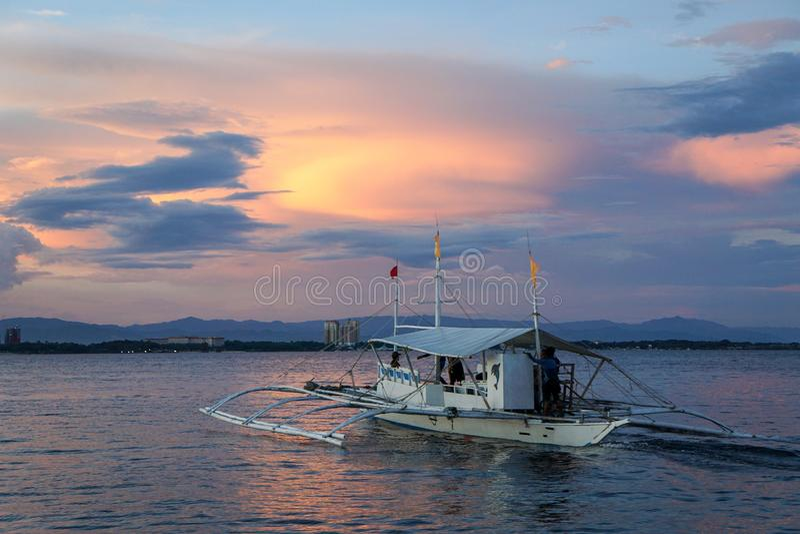 Fischerboot auf Meer bei dem Sonnenuntergang, philippinisch stockbild