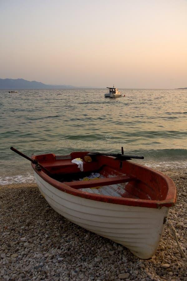 Fischerboot auf Strand am Sonnenuntergang stockbild