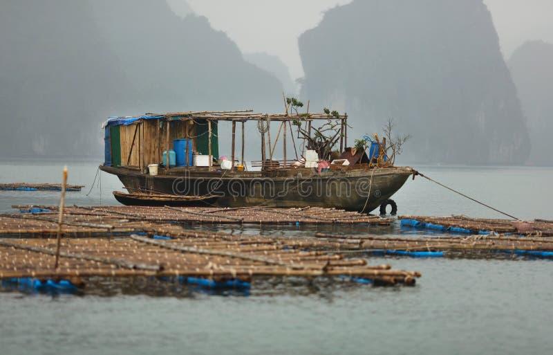 Fischerboot an der Fischfarm im Halong Schacht, Vietnam lizenzfreie stockfotografie
