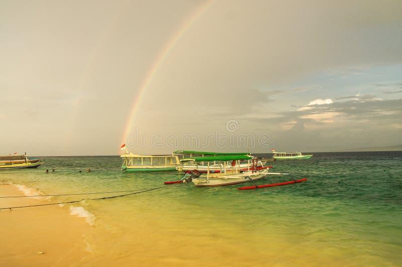 Fischerboot festgemacht auf dem sandigen Strand von Gili Meno-Insel auf dem Hintergrund des Regenbogens indonesien stockfoto