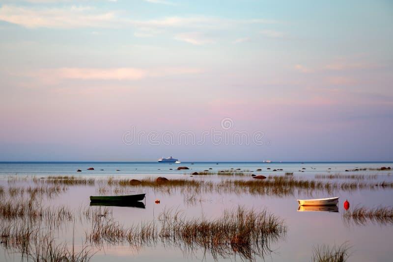 Fischerboot im klaren See bei Sonnenuntergang Szenische Ansicht lizenzfreie stockfotos