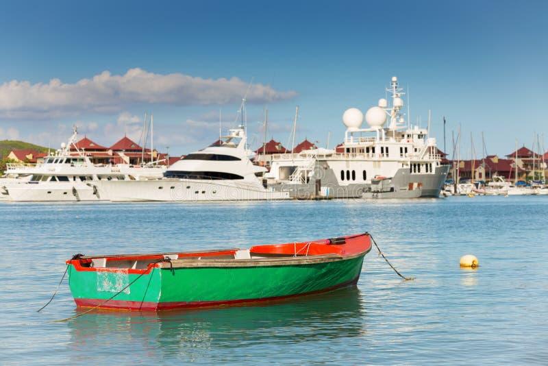 Fischerboot mit luxuriösen Yachten Hintergrund, Eden Island, Milliamperestunde stockfotos