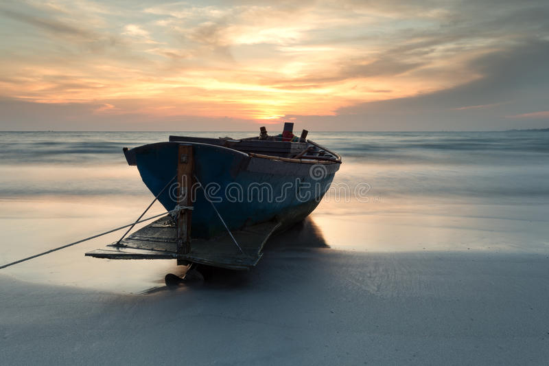 Fischerboot am Strand während des Sonnenuntergangs stockfoto