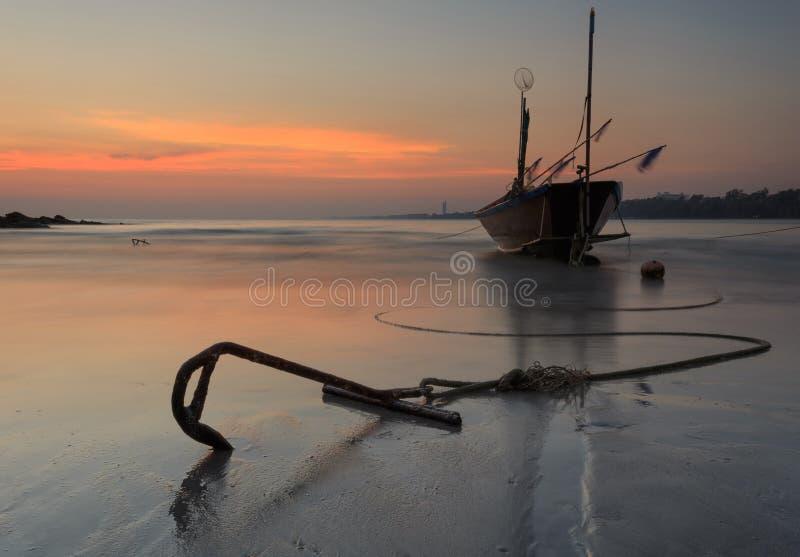 Fischerboot am Strand während des Sonnenuntergangs lizenzfreie stockfotografie