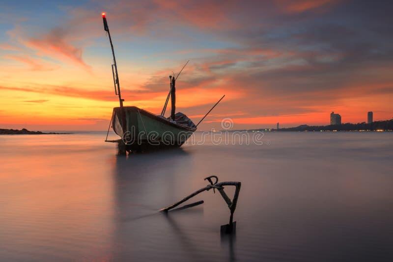 Fischerboot am Strand während des Sonnenuntergangs stockfotografie