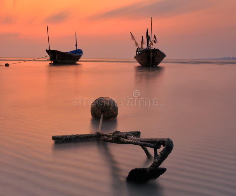Fischerboot am Strand während des Sonnenuntergangs stockbild