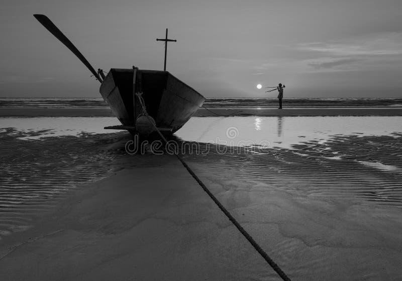 Fischerboot am Strand während des Sonnenuntergangs in Schwarzweiss lizenzfreies stockfoto