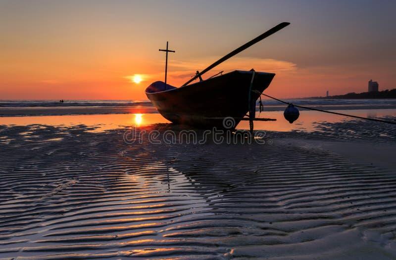 Fischerboot am Strand während des Sonnenuntergangs, Thailand lizenzfreie stockbilder