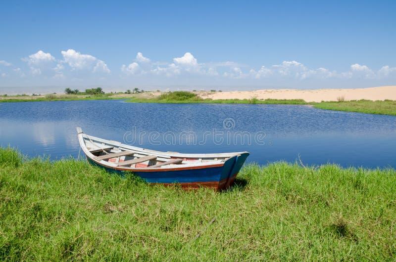 Fischerboot verankert in der Lagune mit grünem Gras und Dünen lizenzfreie stockfotos