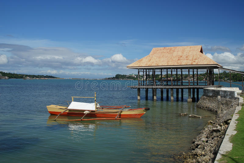 Fischerboote Banca machten weg von Dauis, Panglao, Bohol, Philippinen mit Tagbilaran im Hintergrund fest stockbilder
