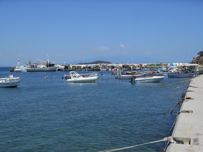 Fischerboote, die auf Meer nahe Seedock in Olympiada schwimmen stockfotografie