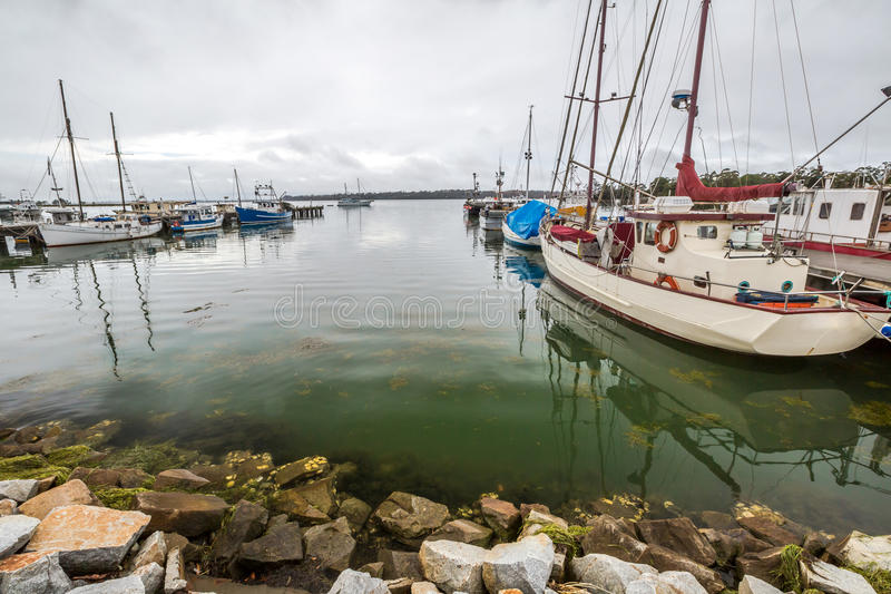 Fischerboote reflektieren sich, Bucht von Feuern, Tasmanien stockbilder