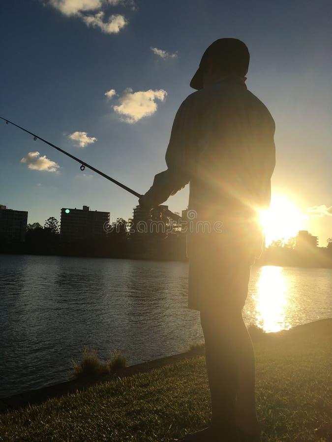 Fischerei bei Sonnenuntergang lizenzfreie stockbilder