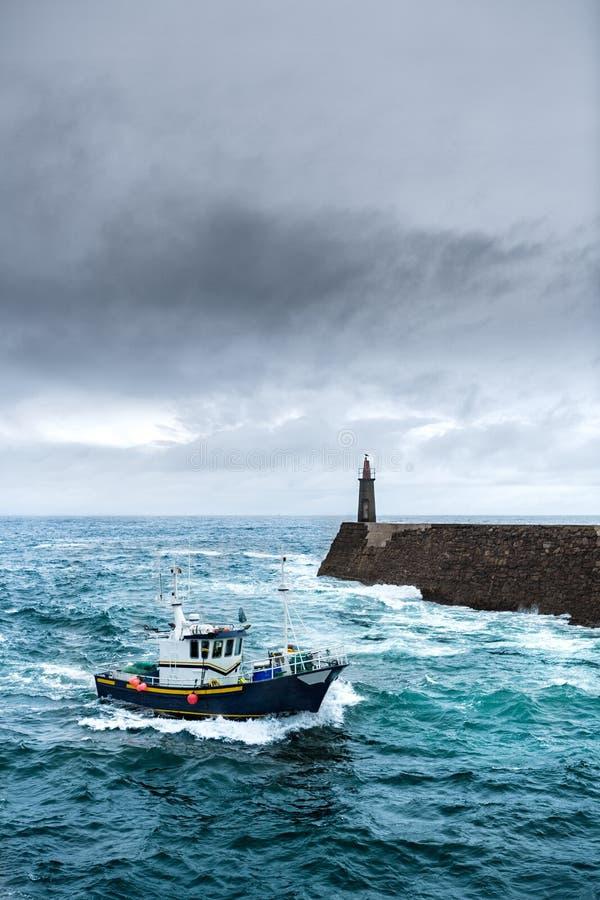 Fischerei-Fahrzeug unter dem Sturm, der im Pier ankommt stockbild