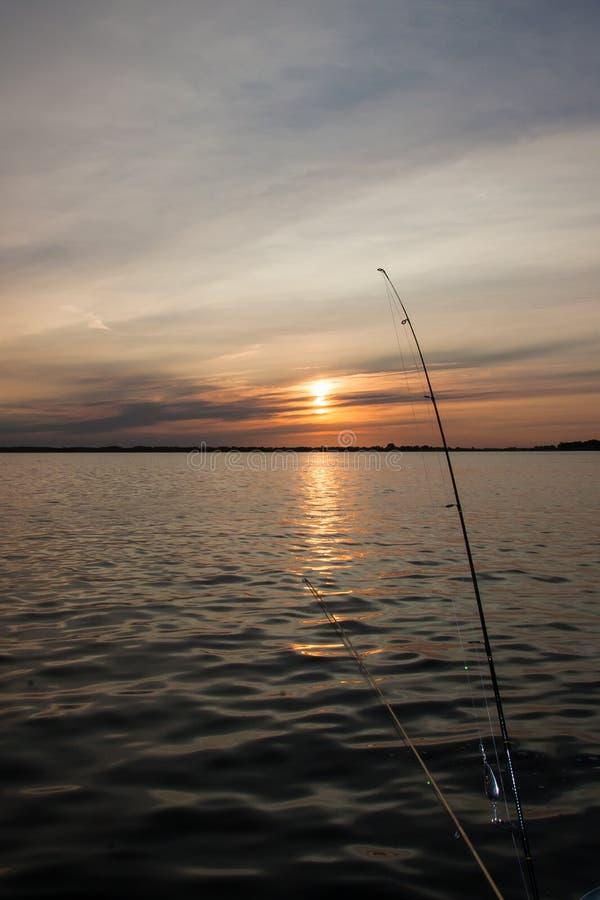 Fischerei Polen am Sonnenuntergang lizenzfreie stockbilder