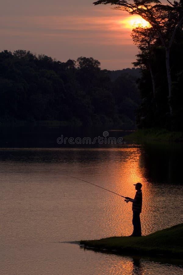 Fischerei am Sonnenuntergang lizenzfreies stockbild