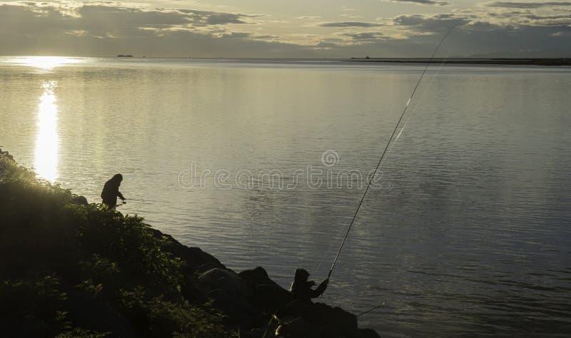 Fischerei unter Sonnenuntergang stockfotografie