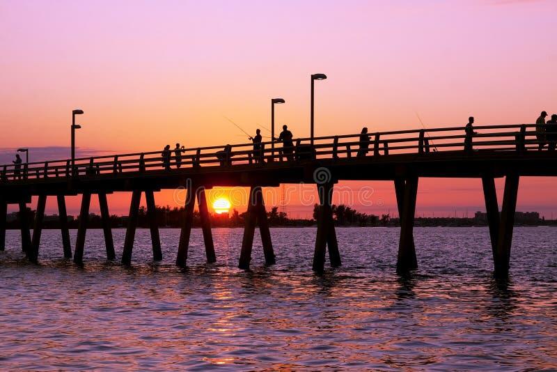 Fischerei weg vom Pier am Sonnenuntergang lizenzfreies stockbild