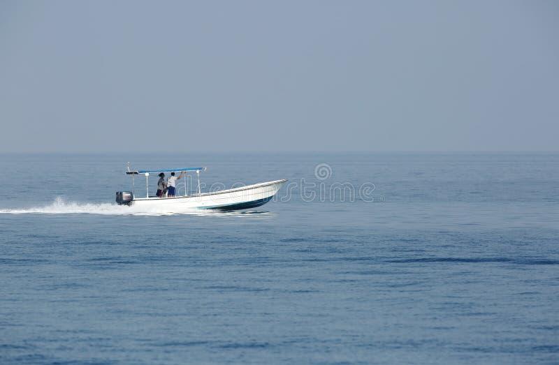 Fischermänner des frühen Morgens, die in Meer auf Schnellboot umziehen lizenzfreies stockbild