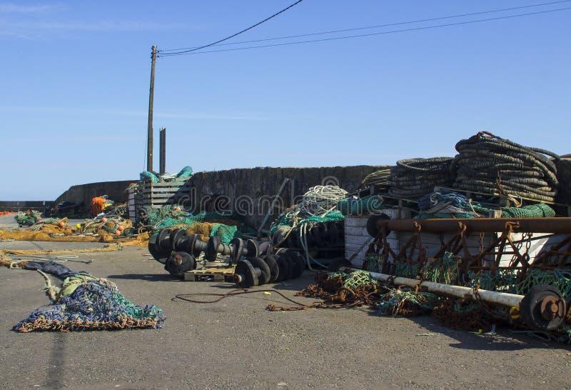 Fischernetze und Hummertöpfe unten gespeichert auf dem Kai und gegen die Hafenwand bei Kilkeel in der Grafschaft Nordirland stockfoto