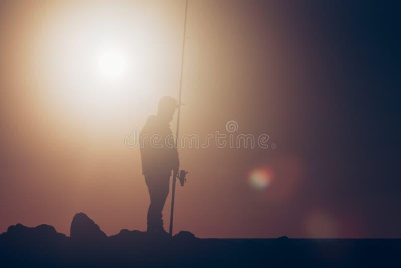 Fischerschattenbild, das während der heißen Sommersonne fischt lizenzfreies stockbild