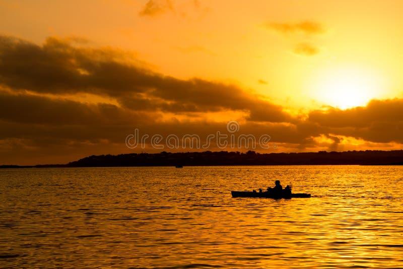 Fischerschattenbild im Kajak und im Seesonnenuntergang lizenzfreie stockfotos