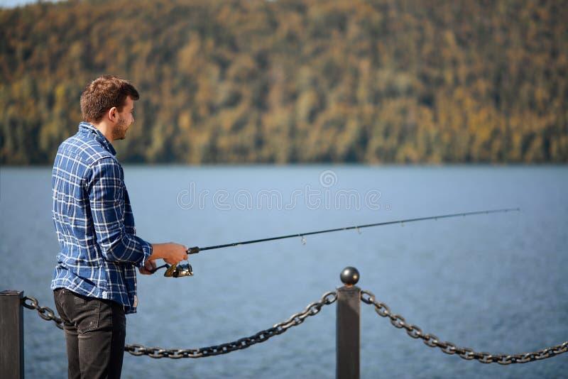 Fischerstellung auf Flussufer und Versuchen, Fische zu fangen lizenzfreie stockfotos