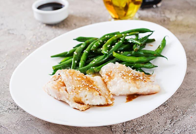 Fischfilet diente mit Sojasoße und grünen Bohnen in der weißen Platte lizenzfreie stockbilder
