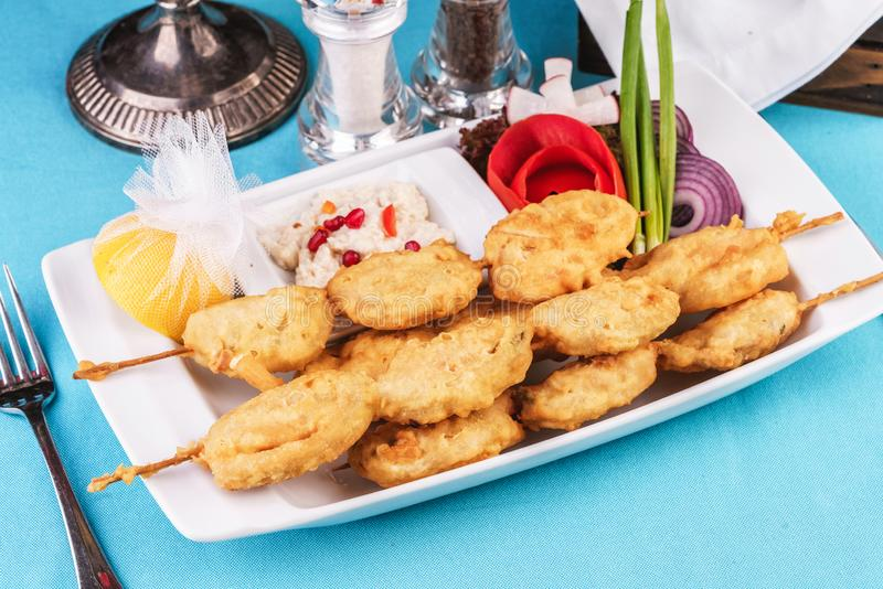 Fischfleischskebab mit Grün, Tomaten, Käse und roten Zwiebeln mit Sahne-Sauce lizenzfreies stockbild