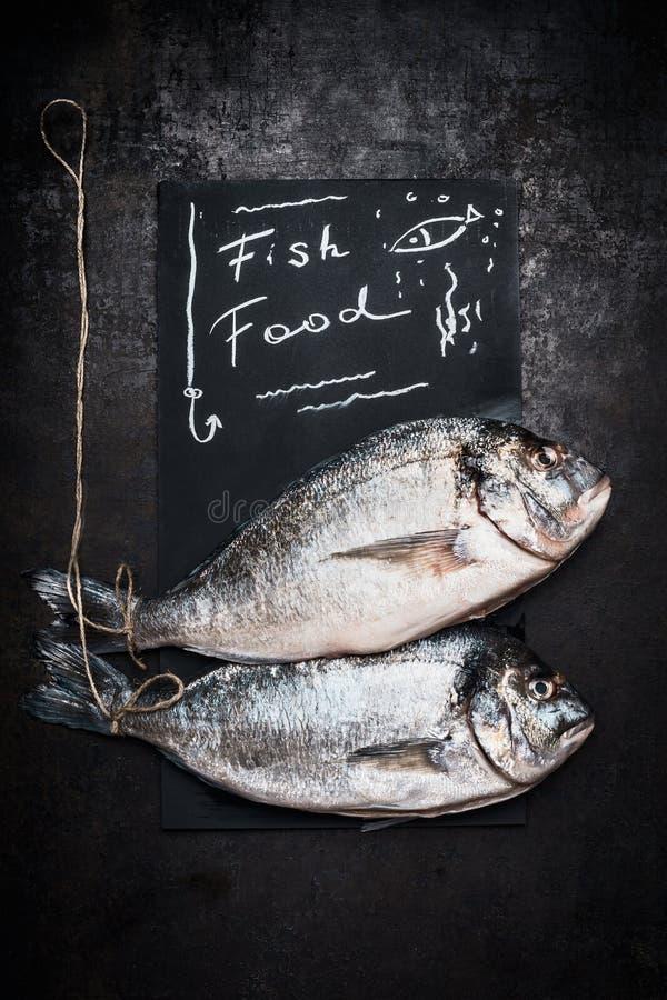 Fischfutterbeschriftung auf schwarzer Tafel mit rohem ganzem dorado zwei fischt auf dunklem Weinlesehintergrund, Draufsicht Meere stockbilder