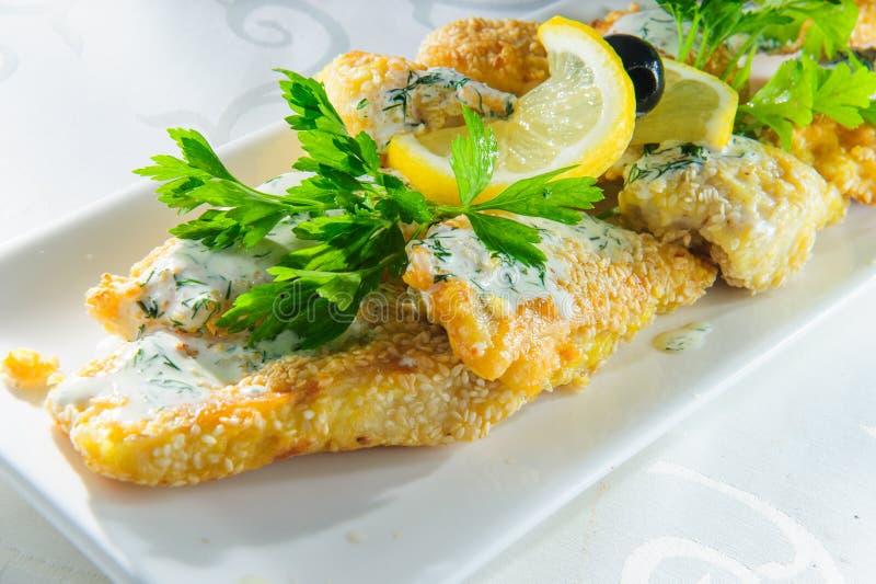 Fischgericht - gebratenes Fischfilet mit Gemüse auf weißem Hintergrund lizenzfreies stockbild