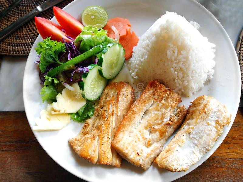 Fischgericht mit seitlichem Gemüsesalat lizenzfreies stockbild