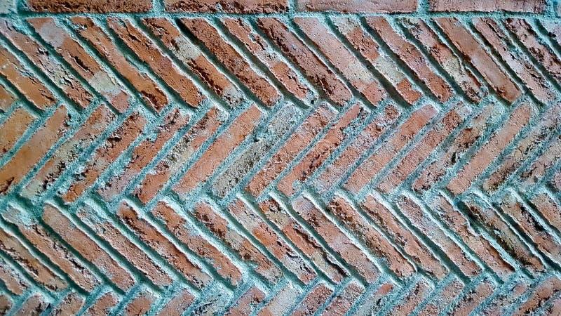 Fischgrätenmusterziegelstein-Musterwand Zementzeigen stockfoto