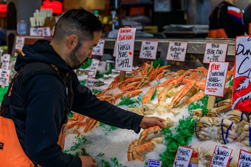 Fischhändler an einem Stall mit frischen Lachsen für Verkauf am Pike-Platz-Markt lizenzfreies stockbild