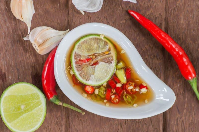Fischsauce mit Scheibenkalkscharfem paprika in der weißen Schüssel mit Kalk, Knoblauch und glühendem Paprika auf Holztisch stockfoto