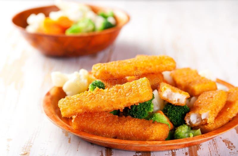 Fischstäbchen mit seitlichem Teller des Gemüses lizenzfreies stockfoto