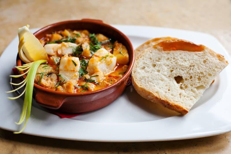 Fischsuppe mit Kabeljau Appetitanregender spanischer Teller aller i-pebre in einer Lehmplatte mit Zitrone und eine Scheibe brot K stockbild