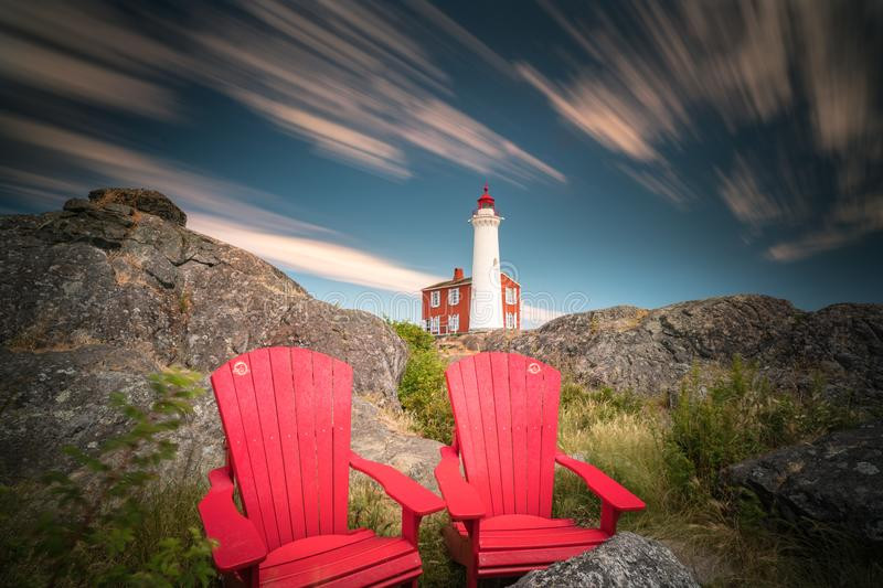 Fisgard Lighthouse and red chairs long exposure. This is a long exposure of the Fisgard Lighthouse with red chairs in the foreground royalty free stock photography