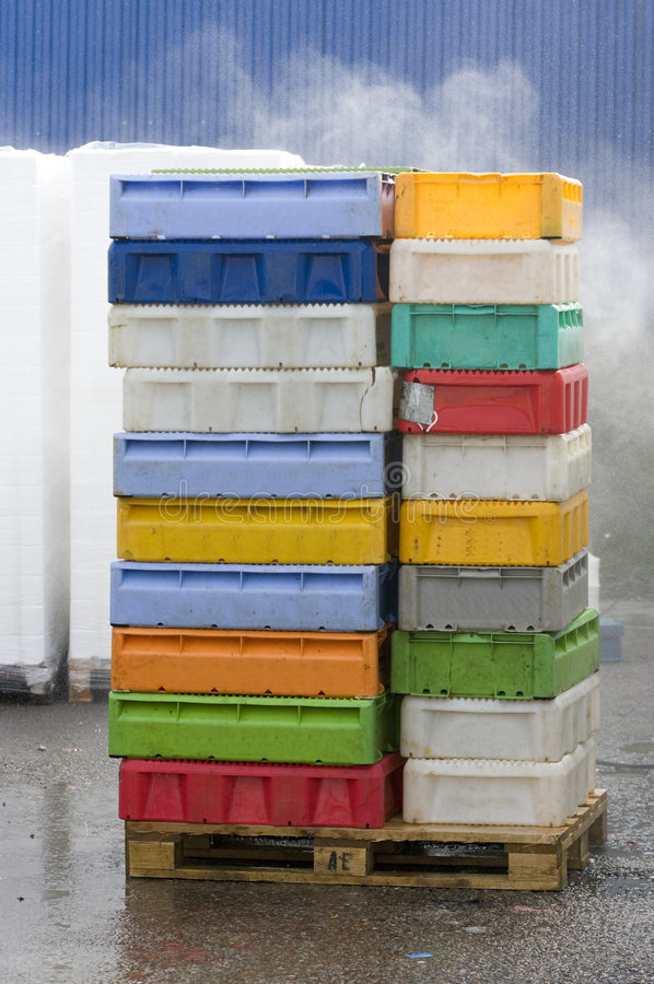 Fish boxes pile. A pile of colorful plastic fish containers being cleaned with water stock photo