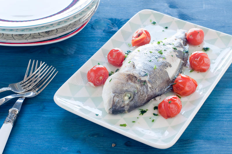 Fish bream cooked in crazy water, typical recipe of southern Italy with sea water, tomatoes, onions and garlic. Italy stock image