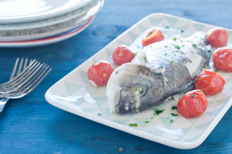 Fish bream cooked in crazy water, typical recipe of southern Italy with sea water, tomatoes, onions and garlic. Italy stock photos