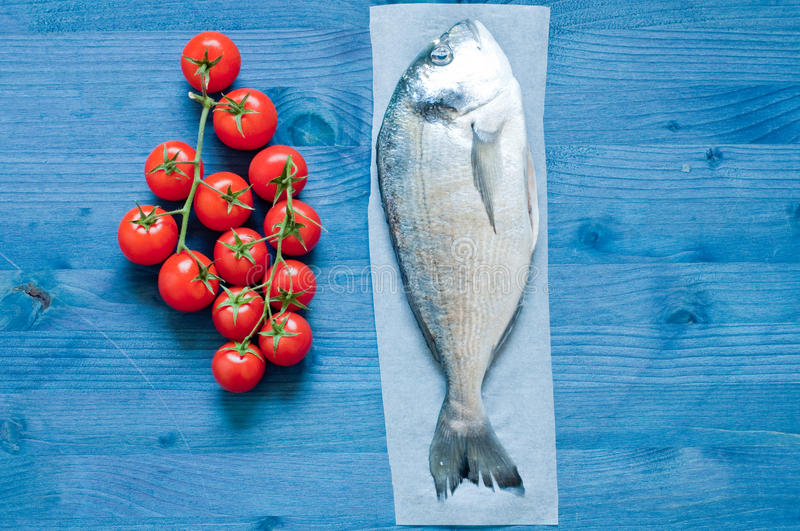 Fish bream cooked in crazy water, typical recipe of southern Italy with sea water, tomatoes, onions and garlic. Italy royalty free stock image